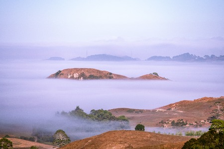 A thick fog covering the hills creating islands