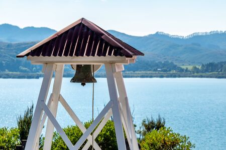 A christian church bell with the sea in the background