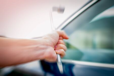 A troubled young person breaking into a car with a crowbar Imagens