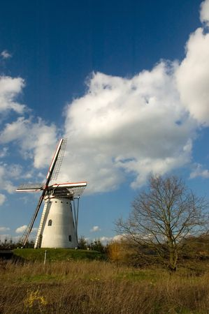 Detail of a windmill in a small dutch town under a clouded sky photo