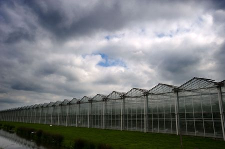 A glasshouse growing fresh vegetables under a dramatic storm sky Stock Photo
