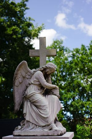 Statue on graveyard of angel with wings carrying a cross