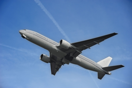 A gray Boeing 777 airplane taking off from an airport Stock Photo
