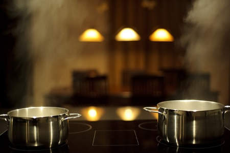 Two stainless steel pots on a induction stove with steam, table on background photo