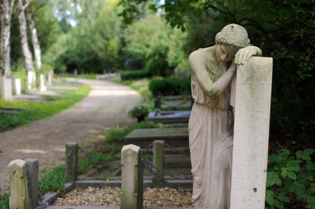 Statue of sad girl on a grave at a cemetery