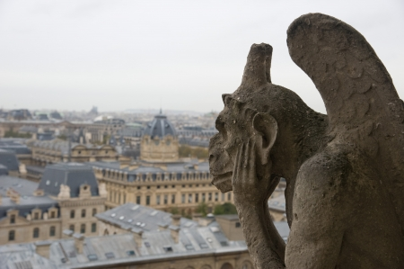 chimera: Stone gargoyle (Chimera) overlooking the city of Paris from the tower of the Notre Dame Stock Photo