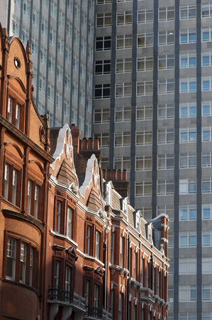 Row of old houses in front of a modern office building in London, UK