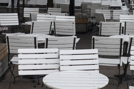 Bunch of white chairs and tables on an outside terrace of a bar