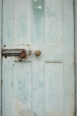 Old closed and locked shaded green door Stock Photo