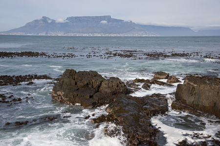 Rocky beach with  the sea in South Africa and mountain in the background