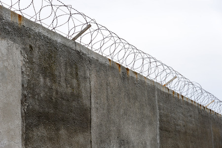 Concrete grey prison wall with barb wire