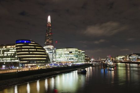 Skyline of London at night from the river Thames