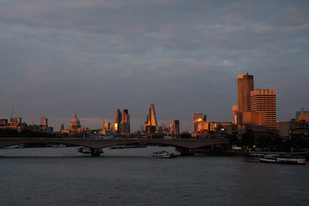 Skyline of London seen from the river Thames at dusk