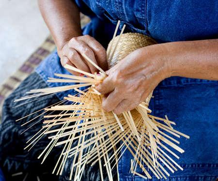 female hands manuallyweaving bamboo basket