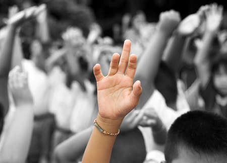 raising hand: hand in color raised among others hands in black and white background