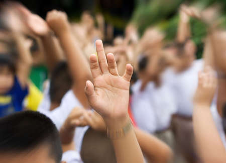raising hands: sharp hand raised in blury schoolyard background zooming in Stock Photo