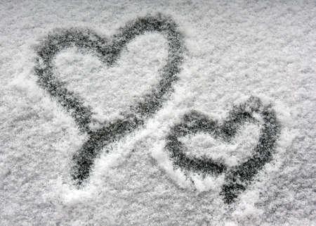 two hearts on snowy window photo