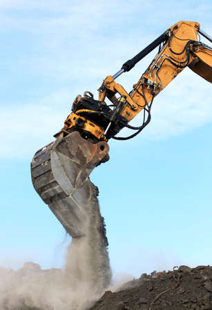 excavator arm and bucket scoop full of dirt at construction site photo