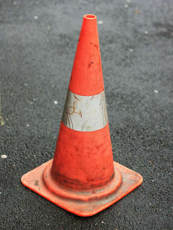 under control: orange traffic cone placed in city street Stock Photo