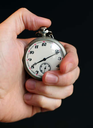 hand holding stop-watch over dark background photo