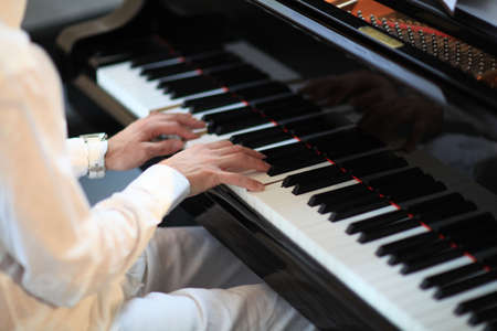 man with white shirt and trousers playing grand piano photo