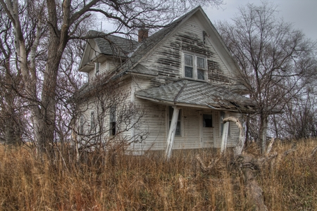 An Abandoned Farm House in Rural South Dakota Agricultural Country loses against to the Elements