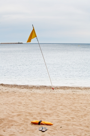 Beach Guard flag, float and flip flops in the sand of the sea Stock Photo - 15142933
