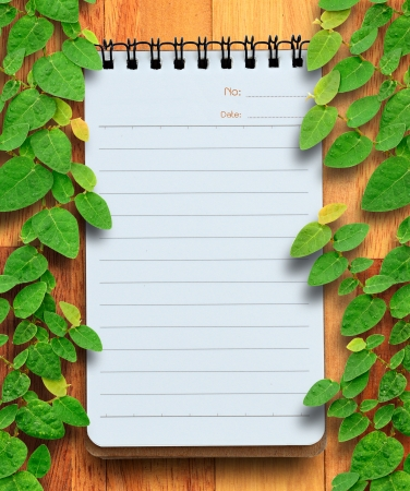 Blank planning notebook on wood background with ivy fixing tree  Conservation concept  photo