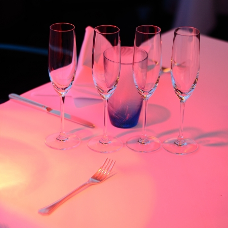 low light: Empty glasses on dinner table indoor in low light. Stock Photo