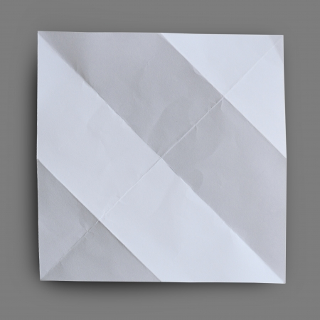 Folded  white paper with wrinkle on gray background. Stock Photo - 19417059