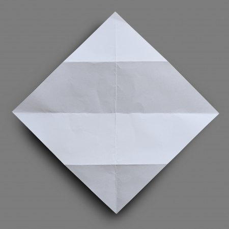 Folded  white paper with wrinkle on gray background. Stock Photo - 19416971