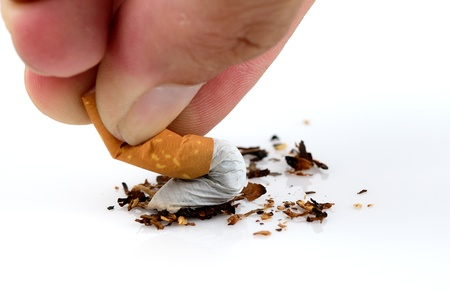 Cigarette being crushed by fingers in stopping smoking concept.  photo