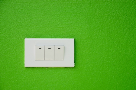 Electrical white rocker light switch on green wall.  photo
