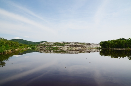 water recycling: Landscape of garbage dump reflection on water and blue sky. Stock Photo