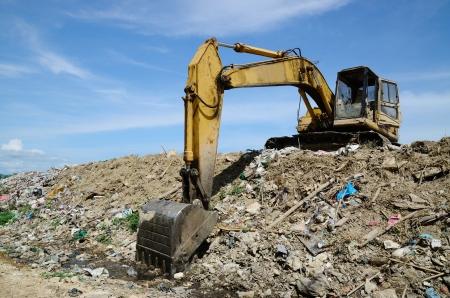 dumps: Backhoe at garbage dump with blue sky.