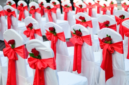 Wedding chairs decorated in white, red ribbons and red rose.