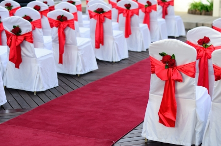 Wedding chairs decorated in white, red ribbons and red rose and pave way with carpet.