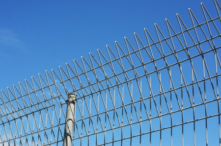 Fench with barb wire and blue sky photo
