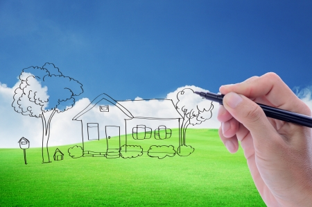 Mans hand sketching house on beautiful green field with blue sky and white cloud background