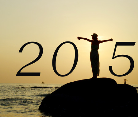 strecthing: Beautiful asian woman standing, streching hands, on stone silhouetted the sunrise in morning scene with year 2015 calendar.