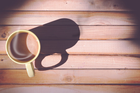 strong light: Hot coffee with morning sunlight, wood panel background. Vintage style, top view, strong light with shadow.