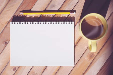 strong light: Blank sketch notepad with pencil and hot coffee in morning sunlight. Vintage style, top view, strong light with shadow.