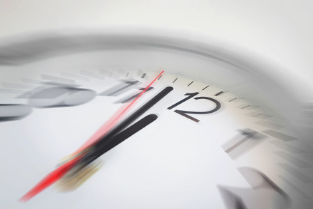 Close up of the hands of clock pointing nearly at 12 o'clock, business concept on deadline or rush hour. Using radial blur effect at 12 o'clock and rest is blurred. Foto de archivo