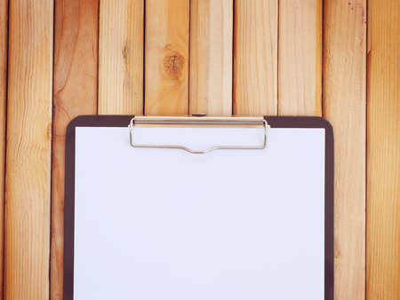 wood panel: Blank white paper attach with black clipboard on wood panel background. Vintage style. Top view.