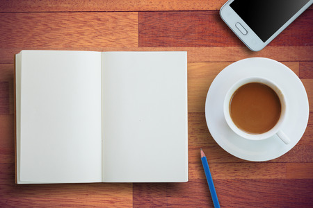 libro abierto: la hora del café con el libro abierto de color blanco, concepto de negocio en la planificación y conseguir idea. Fondo de madera con estilo de la vendimia.