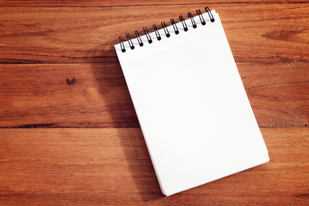 Blank notebook or notepad on wood background.