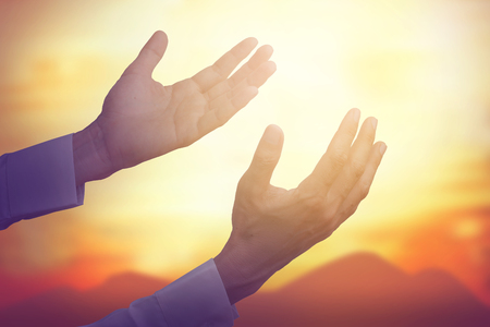 pray: Two mans hand, palm upward to reach the sky to pray for God, concept of pray for God or make worship. Warm sunshine tone, vintage filter, glow light effect.