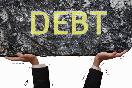 financial burden: Busines man hand carrying and making effort to push up big stone with message DEBT. Business concept on trouple situation in debt burden.