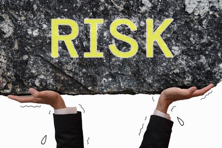 risk taking: Busines man hand carrying and making effort to push up big stone with message RISK. Business concept on taking risk situation.