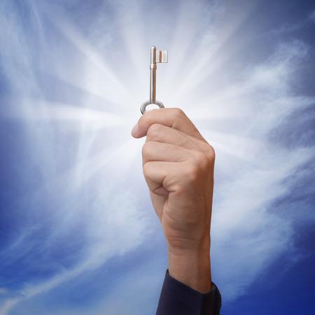 llave de sol: hombre de negocios que sostiene y elevar clave en el aire con rayos de sol brillando detr�s, met�fora para el concepto de negocio en tener soluci�n clave para la resoluci�n de problemas.